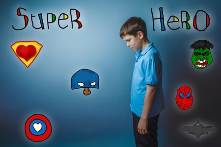 bowed head: Teen boy bowed his head turned sideways and looking down superhero super power at the photo studio Icons hero