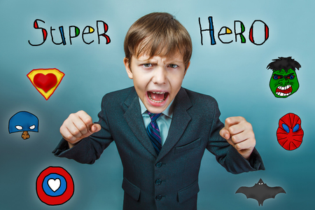 opened mouth: Teen boy businessman clenched fists and shouts opened his mouth anger angry superhero super power at the photo studio Icons hero