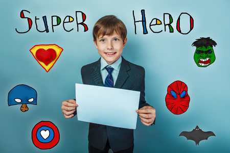 laughs: Teen boy businessman holding a piece of paper and laughs superhero super power at the photo studio Icons hero Stock Photo