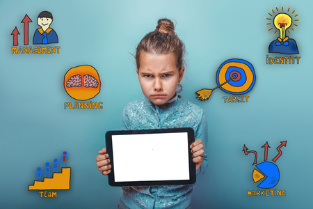 frowned: teen girl frowned and holds the tablet in the hands of a collection of business icons management team goal sketch Stock Photo