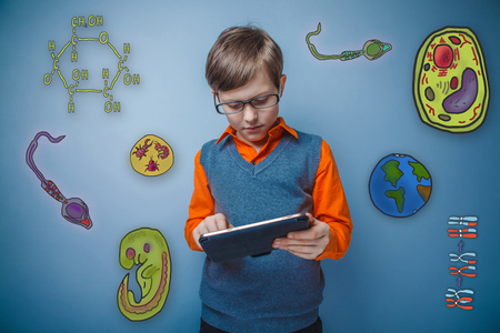 enthusiastically: Teenage boy in glasses enthusiastically working on the tablet to think seriously icons biology education formation of the embryo cell parasite Stock Photo