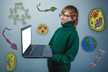 parasite: Teenage boy in glasses holding a laptop in hands and laughs icons biology education formation of the embryo cell parasite Stock Photo