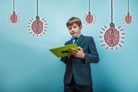 brain works: adolescent boy official style works on the tablet brain bulb creative idea Stock Photo