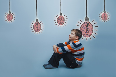hugging knees: adolescent boy sitting on the floor hugging his knees smiling looking at the brain bulb creative idea