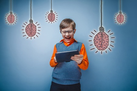 adolescent: adolescent boy with glasses Retro Style laughing and working on a tablet brain bulb creative idea