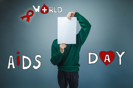 boy in green sweater covered his face with a white sheet of paper the International AIDS Day