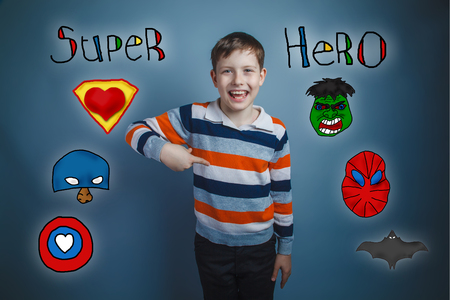 laughs: Teen boy points his finger down and laughs superhero super power at the photo studio Icons hero