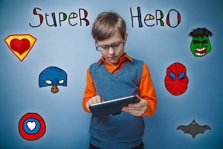 enthusiastically: Teen boy retro style works enthusiastically on the tablet superhero super power of the photo studio Icons hero