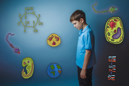 frowned: Teen boy lowered his head frowned looking down icons biology education formation of the embryo cell parasite Stock Photo