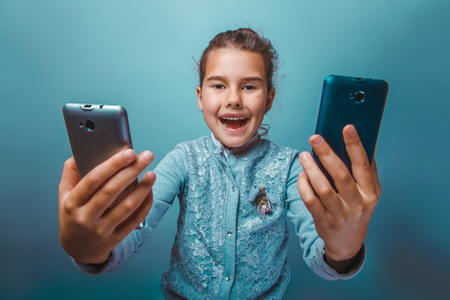 seven years: teen  girl of European  appearance seven years, holding  two telephones opened her mouth on a gray background Stock Photo