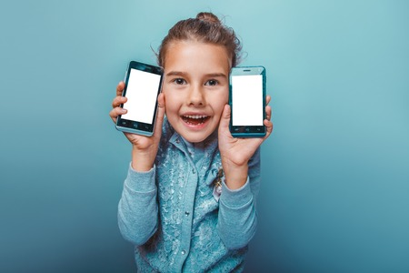 telephones: teen girl  of European  appearance seven years, holding two  telephones opened her mouth on a gray  background Stock Photo