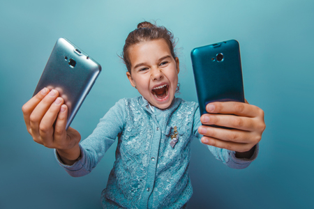 telephones: teen girl of European appearance  seven years, holding two telephones opened her mouth on a gray background