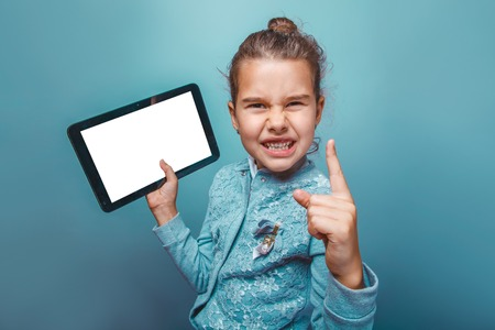 seven years: teen girl of European appearance seven years shows a finger up the angry idea of holding a tablet in the hands on a gray background