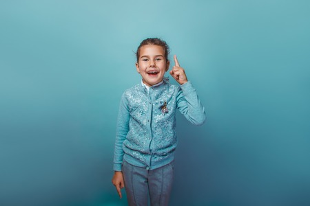 seven years: teen girl of European appearance seven years, the idea has raised the idea a thumbs up open her mouth on a gray background Stock Photo