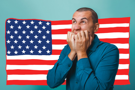 hopelessness: a male businessman closed his mouth with her hands hopelessness fear of an American flag USA Stock Photo