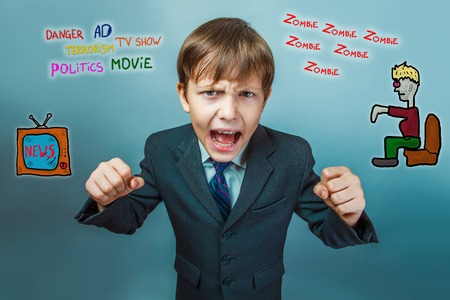 adolescent: adolescent boy screaming clenched his fists media influence zombies tv news Stock Photo