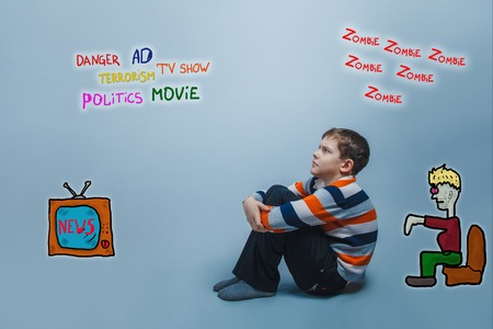 adolescent: adolescent boy sitting looking up media influence zombies tv news Stock Photo