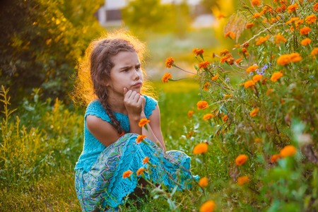seven years: teen girl of European appearance seven years dissatisfied with flowers in nature
