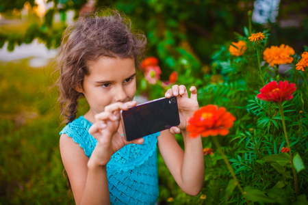 seven years: teen girl of European appearance seven years photographing flowers on the phone on nature