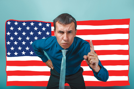 frowned: a male frowned angry businessman raised his index finger American flag USA Stock Photo