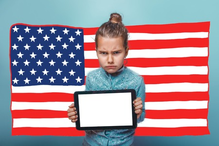 frowned: adolescence girl holding a tablet frowned American flag USA Stock Photo
