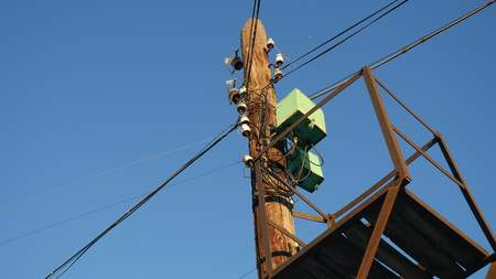telephone poles: Old electric pole with wires on background of blue sky Stock Photo