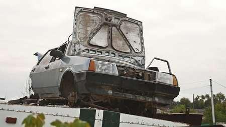 Car dump an old car with an open hood Stock Photo