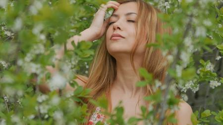 girl closes her eyes among flowering branches