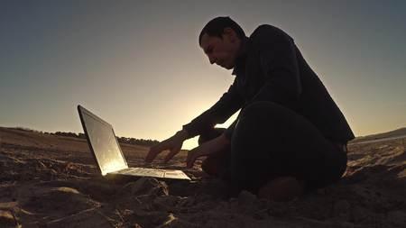 freelancing: man laptop businessman freelancer working behind sitting on beach freelancing silhouette in the sun Stock Photo
