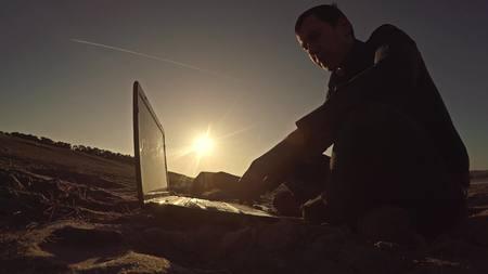 freelancing: man businessman freelancer laptop working behind sitting on beach freelancing silhouette in the sun