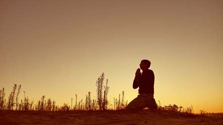 Silhouette illustration of a man praying outside at beautiful landscape Stock Photo