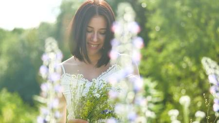 happy girl in a field with flowers in nature. girl in a field smiling woman holding a outdoor bouquet of flowers