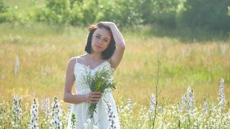 happy girl outdoor in a field with flowers in nature. girl in a field smiling woman holding a bouquet of flowers Stock Photo