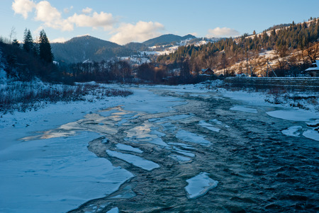 ice covered: Winter Carpathian mountains landscape with ice covered river near village