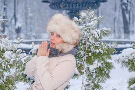 bata blanca: Winter portrait of a woman in white coat during snowfall in a park