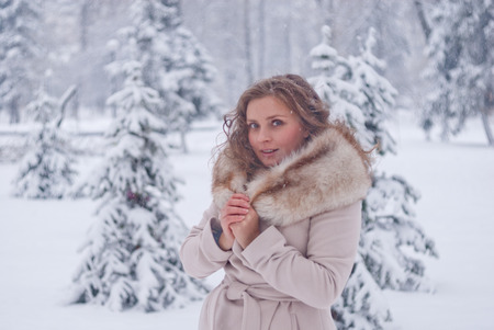 bata blanca: Retrato del invierno de una mujer en bata blanca durante las nevadas en un parque
