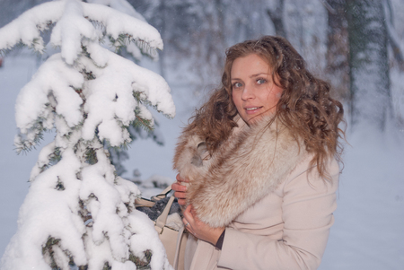 Winter portrait of a woman in white coat during snowfall in a park