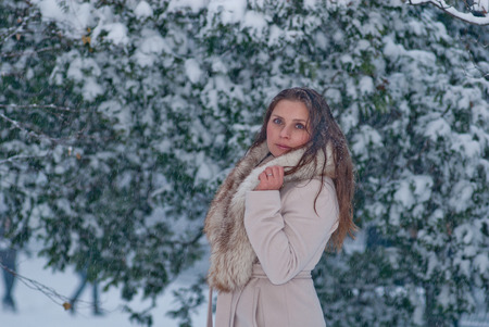 bata blanca: Winter portrain of a woman in white coat during snowfall in the park
