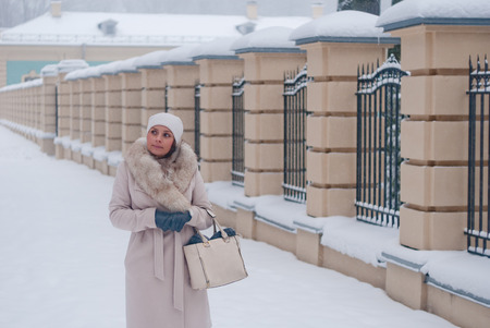winter park: Winter portrain of a woman in white coat during snowfall in the park