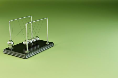 Perpetual motion. Pendulum on green background. 3d photo