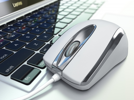 computer equipment: Computer mouse on laptop keyboard. Three-dimensioanl close-up image. Stock Photo