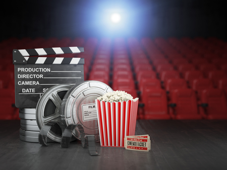 Cinema, movie or home video concept background. Film reels, clapper board  and pop corn in the theater movie cinema screen with empty seats. 3d illustration Stock Photo