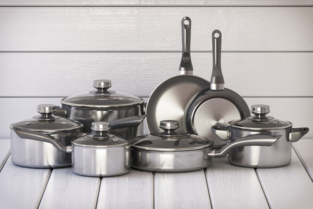 Set of stainless pots and pan with glass lids on the white wooden background. 3d illustration 免版税图像