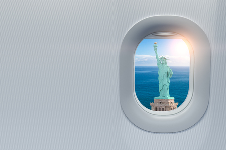 Airplane window with view on Statue of Liberty, New York, USA.