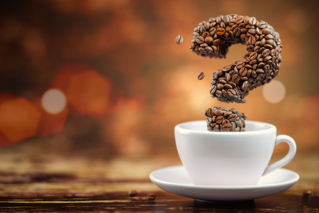 Coffee beans in a form of question mark and white cup.