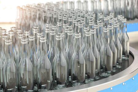 Empty  glass bottles on conveyor belt in factory or glass manufacture. 版權商用圖片