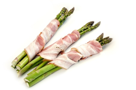 Asparagus wrapped in bacon on a white background. photo