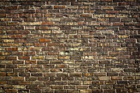 Leeftijd, zwengel en vuile lichtbruine bakstenen muur
