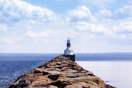 Old white lighthouse with cloudy blue sky photo