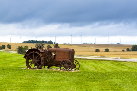 iowa: Old rusty tractor with wind turbines in the background.